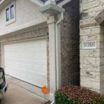 brick house in Texas with gutters and garage door